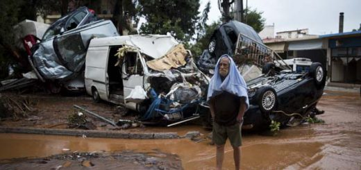 A barefoot man stands in front of a pile of vehicles in the municipality of Madra western Athens, on Wednesday, Nov. 15, 2017. Flash floods in the Greek capital's western outskirts Wednesday turned roads into raging torrents of mud and debris, killing at least nine people, inundating homes and businesses and knocking out a section of a highway. (AP Photo/Petros Giannakouris)