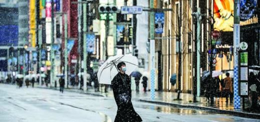 Man, wearing protective face mask, walks on Ginza boulevard during a snowfall in Tokyo